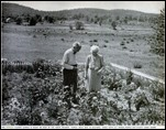 TWB and his wife in their garden with the Purple Hills and Green Meadows behind him